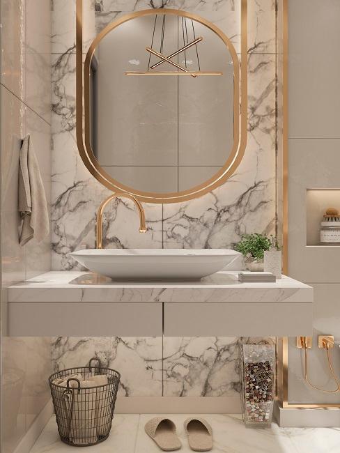Goldener Spiegel an Marmorwand über Waschbecken