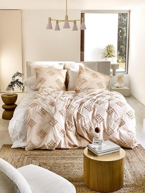 Bett in hellem Schlafzimmer mit beige und weißer Bettdecke