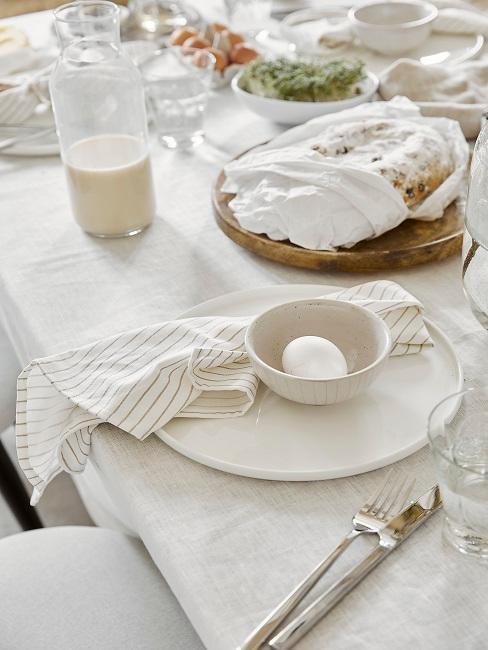 Gedeckter Tisch mit Osterei in einer Schüssel