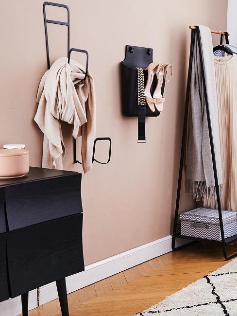 Schwarze Garderobe Elemente vor einer hellrosa Wand