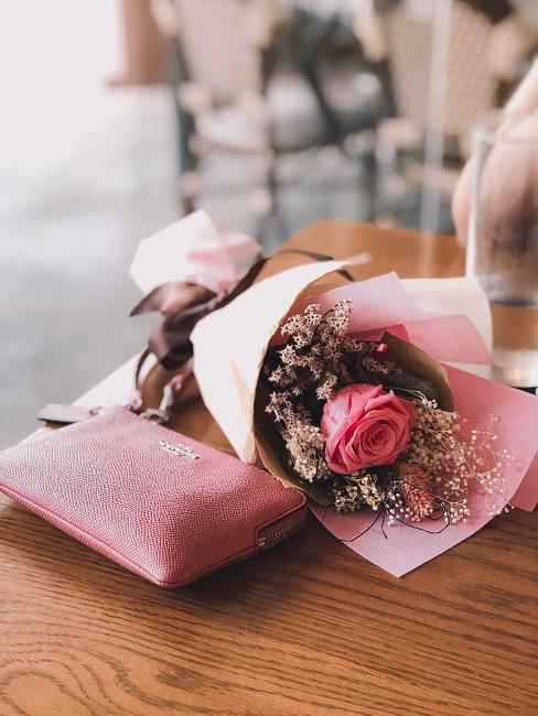 Pinkfarbene Rose neben rosafarbenem Geldbeutel auf Tisch