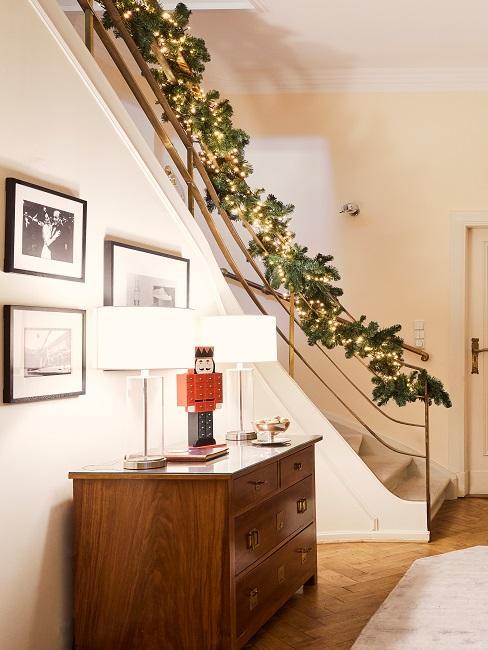 Holzkommode mit zwei Tischlampen neben Treppe mit Zweigen