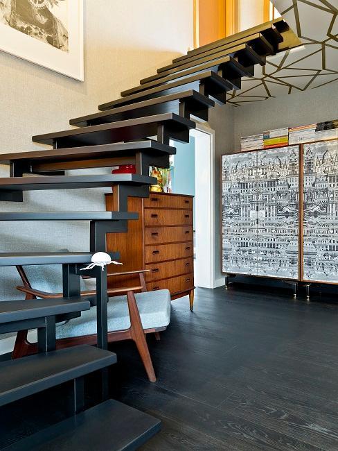 Schwarze offene Treppe über Lesebereich mit Kommode und Sessel