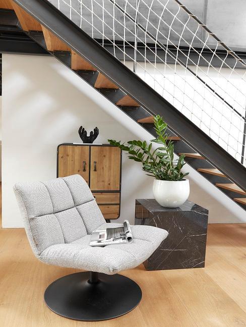 Grauer Sessel neben Marmorbeistelltisch
