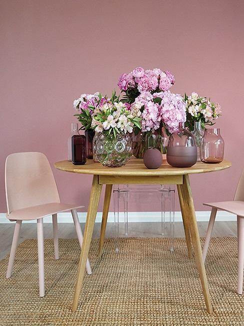 Warme Wandfarbe Altrosa hinter Holztisch mit Blumen