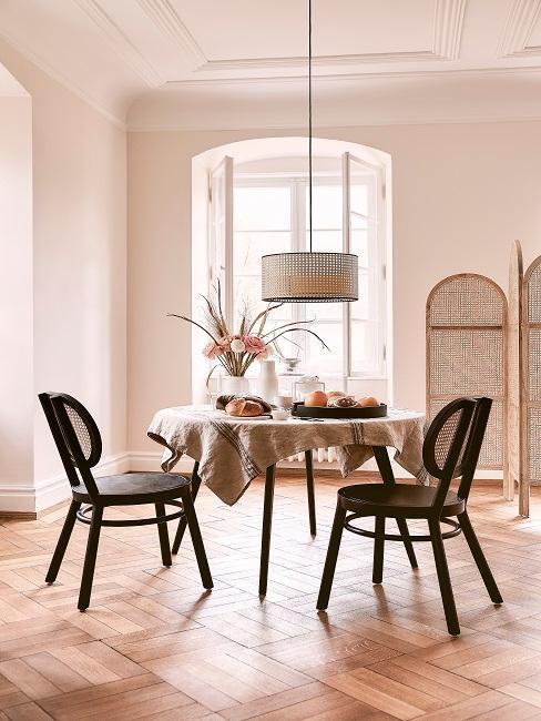 Beiges Esszimmer mit Paravent und schwarzen Stühlen