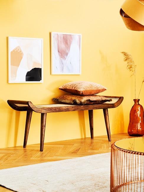 Helle, gelbe Wandfarbe mit Bildern und Holzbank