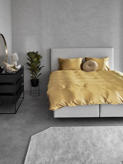 Schlafzimmer mit grauer Wandfarbe, schwarzen Möbeln und gelber Bettwäsche