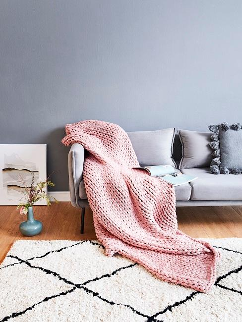 Grau-blaue Wand hinter grauem Sofa mit rosa Decke und cremefarbenem Teppich