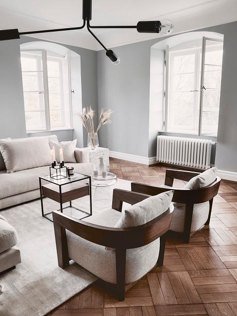 Hellgraue Wände mit cremefarbenen Sesseln und Details aus dunklem Holz