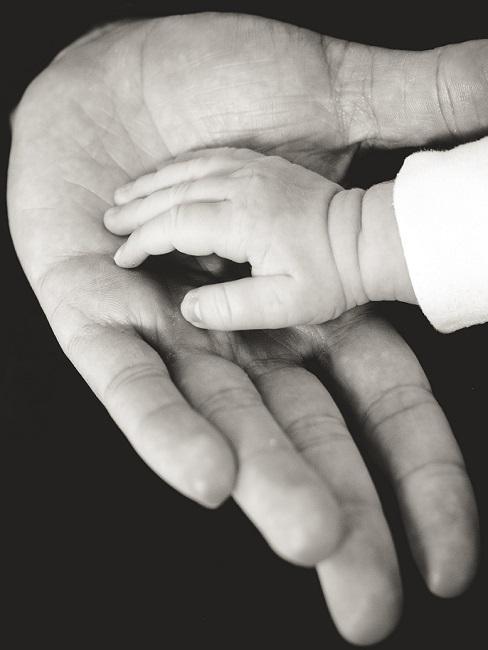 Babyhand auf Hand von Erwachsenem in Schwarz-Weiß