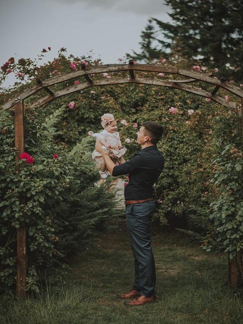 Mann mit Baby im Arm vor Gebüschen