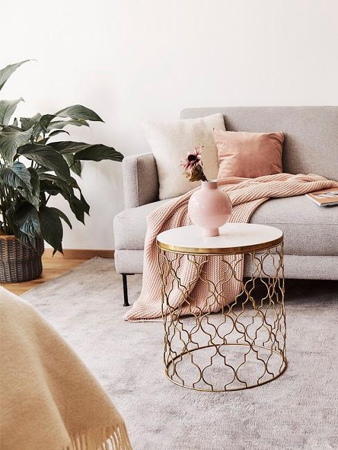 Goldener Couchtisch mit rosa Vase vor grauem Sofa