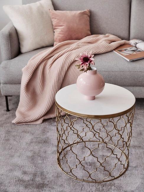 Goldener Couchtisch mit rosa Vase auf grauem Teppich
