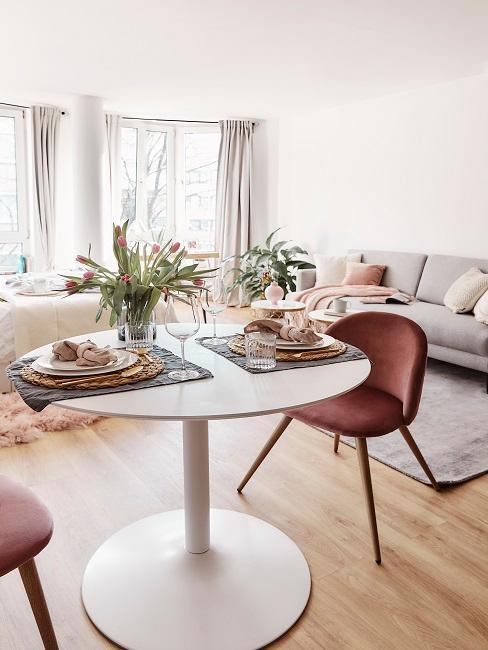 Runder Tisch mit Tischdeko und rosa Stühlen