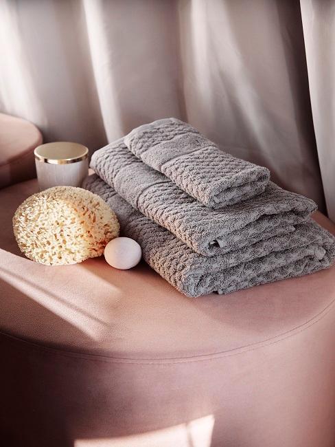 Graue Handtücher auf rosa Pouf