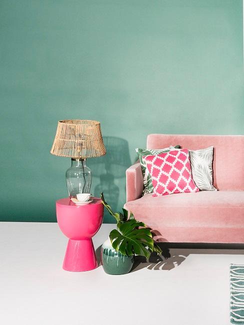 Mitgrüne Wand hinter rosafarbenem Sofa und Beistelltisch