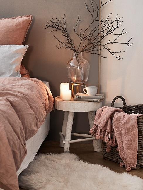 Holzhocker neben Bett mit Kerzen und Glasvase