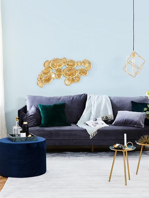 Pastellblaue Wand, dunkelblaues Sofa, goldene Wanddeko