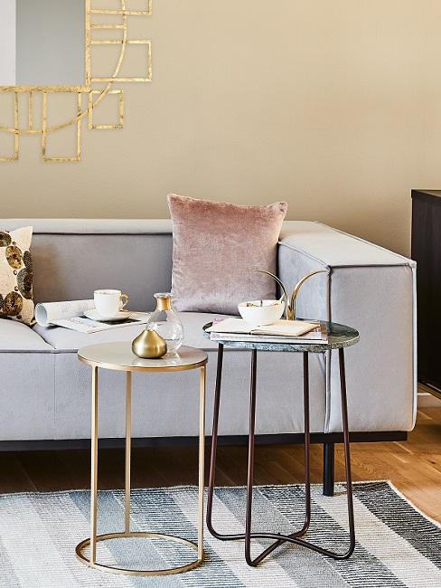 Wandfarbe Pastell Gelb, goldene Accessoires, graues Sofa, Samtkissen