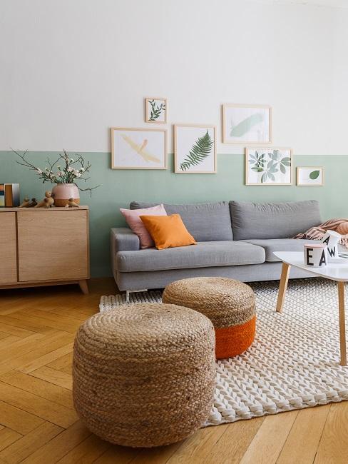 Wohnzimmer mit pastellgrüner Wad, grauem Sofa, Jutepoufs und Holzmöbeln
