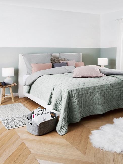 Zweifarbige Wand in Weiß und Pastellgrün in Schlafzimmer mit pastellgrüner Bettwäsche, rosa Kissen und weißem Lammfell am Boden