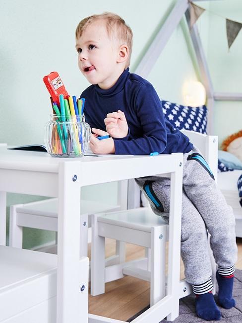 Junge auf Stuhl an Kindertisch