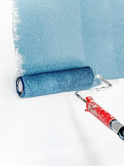 Farbroller streicht blaue Wandfarbe an weiße Wand