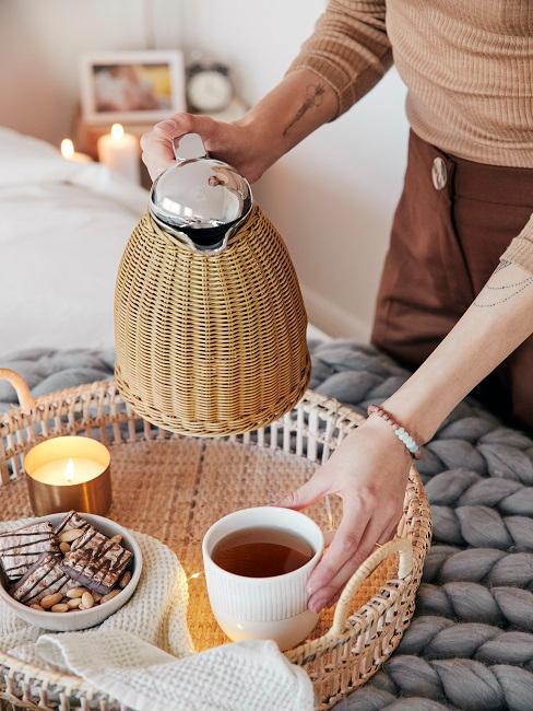 Frau schenkt Tee in Tasse ein