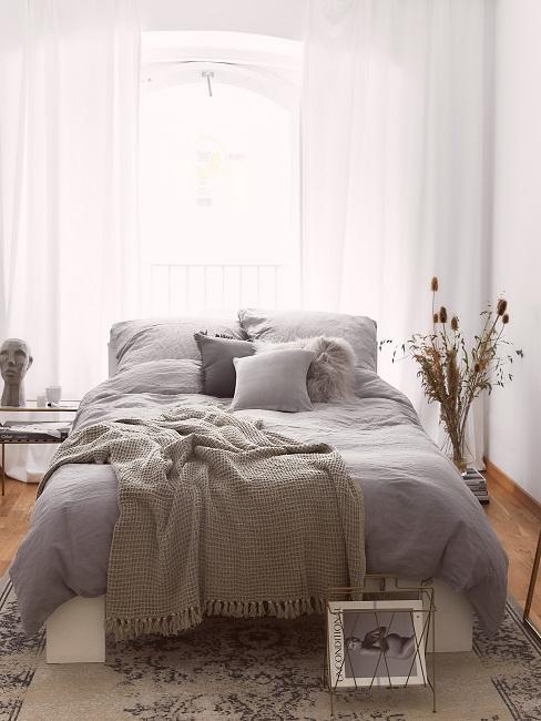 Schlafzimmer mit grauer Bettwäsche aus Leinen und Kissen