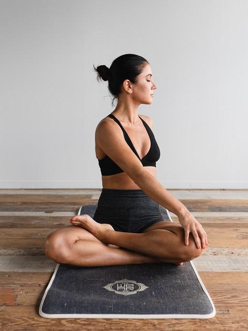Yoga für Zuhause Frau Yogamatte Drehsitz