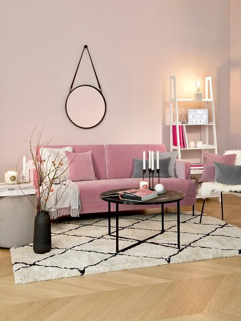 Wohnzimmer mit rosafarbenen Wänden, rosa Sofa, schwarz-weißer Teppich und Akzente in Schwarz
