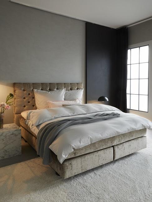 Schlafzimmer mit grauer und schwarzer Wand, beigem Bett und hellgrauem Teppich