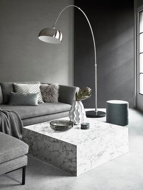Wohnzimmer mit grauer und schwarzer Wand, grauem Sofa, Mamortisch und silbernen Stehleuchte