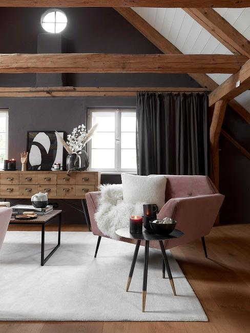 Schwarze Wand mit Holzmöbeln, rosafarbenen Sessel und weißem Teppich