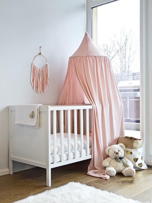 Babyzimmer mit weißer Wandfarbe, weißem Babybett und rosa Deko