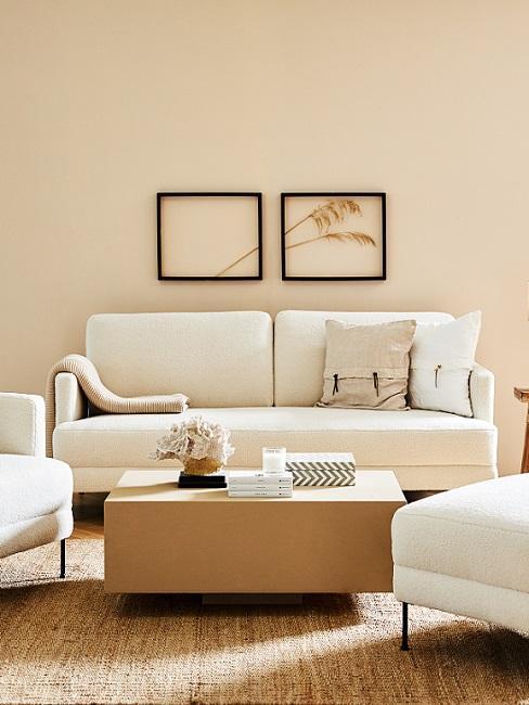 Beigefarbenes Wohnzimmer mit Sofa, Couchtisch und Bildern an der Wand