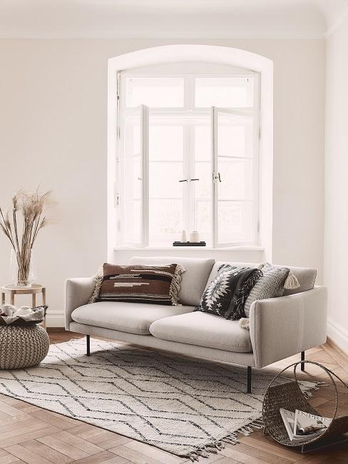 Boho-Wohnzimmer mit beigefarbenen Wänden, Ethno-Kissen auf beigen Sofa und grafischem Teppich