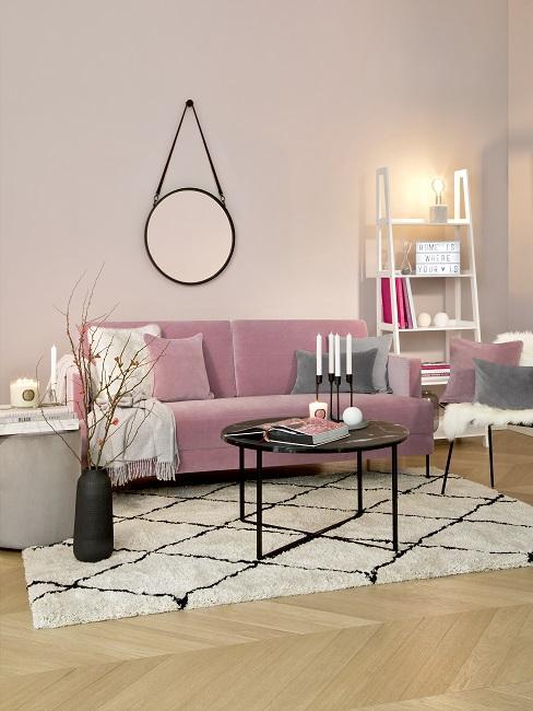 Helle Wandfarbe Rosa in Wohnzimmer mit rosa Sofa, schwarz-weißem Teppich, Schwarzem Tisch und Spiegel