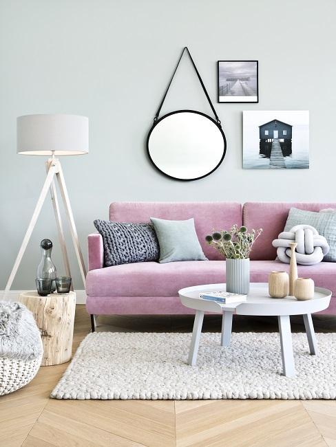 Helle Wandfarbe in Grün im Wohnzimmer mit rosa Soa, weißem Teppich, Lampe und Bilderwand