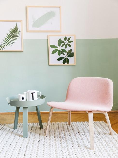 Hellgrüne Wand hinter rosa Stuhl, grauem Beistelltich und Bildern an der Wand