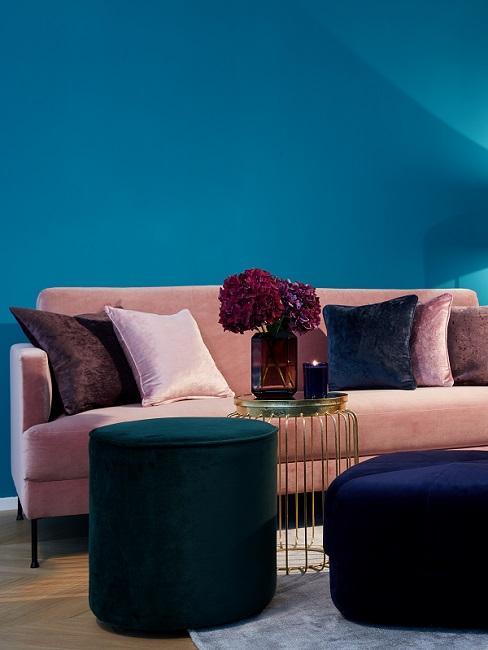 Blaue Wand hinter rosa Couch mit bunten Dekokissen