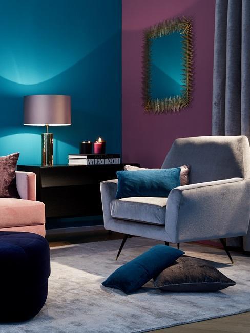Blaue und magentafarbene Wand, hinter grauem Samtsessel und schwarzem Sideboard