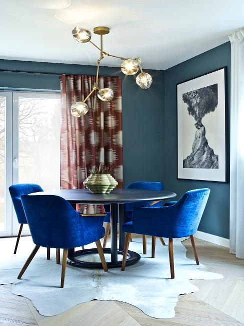 Essbereich mit petrolfarbenen Wänden, dunkelroten Vorhängen, blauen Stühlen und goldener Pendelleuchte