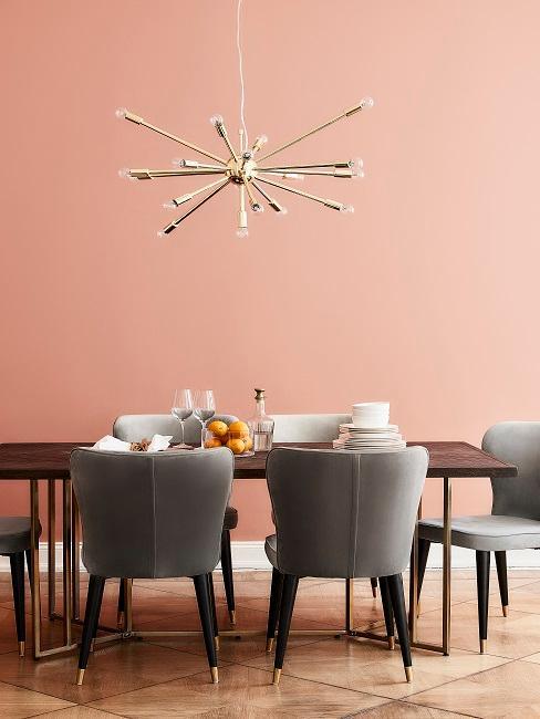 Esszimmer Wandfarbe in Koralle mit dunklem Holztisch, goldenen Pendelleuchte und grauen Samtstühlen