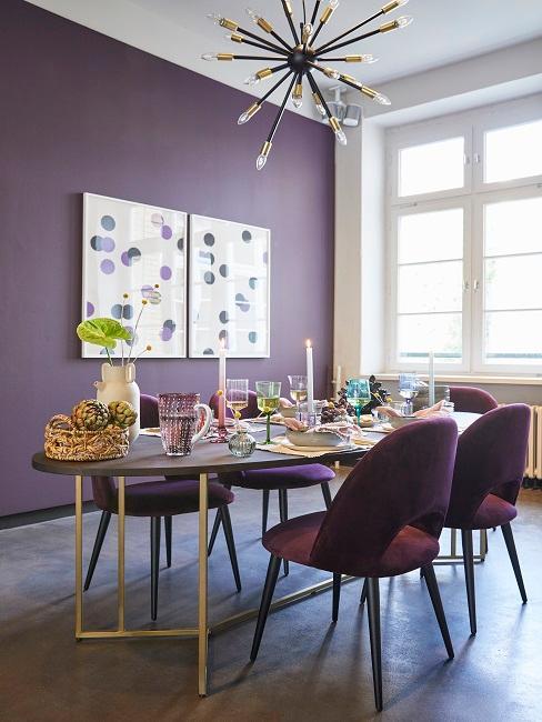 Lila Esszimmer mit braunen Holztisch, violetten Stühlen und weißen Gemälden