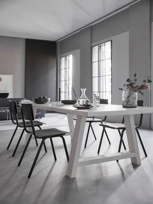Graue Wände im Esszimmer mit weißem Esstisch und schwarze Stühle