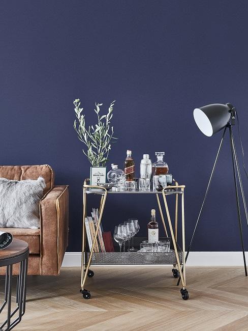 Dunkle Wandfarbe Blau mit braunem Ledersofa, schwarzer Stehlampe und silbernen Servierwagen
