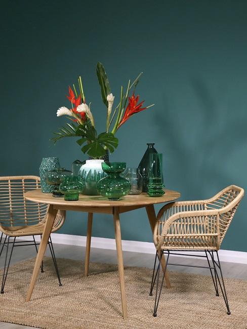 Dunkle Wandfarbe Grün mit Holztisch, Rattanstühlen, Juteteppich und grünen Vasen