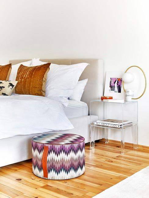 Schlafbereich in erster eigener Wohnung mit Bett, Nachttisch, Kissen und Pouf
